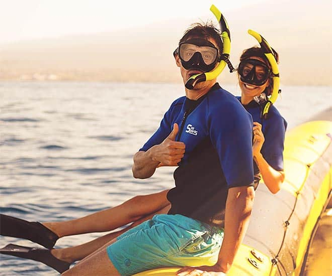 happy snorkelers sitting on the boat at sunset