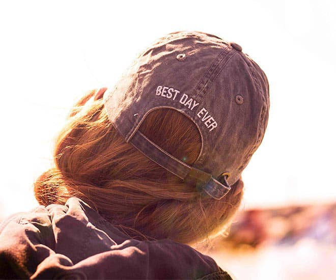 "Woman wearing a hat with ""Best Day Ever"" stitched on the back of the hat"
