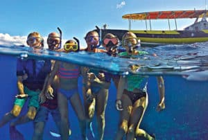 half underwater photo of happy guests in the water