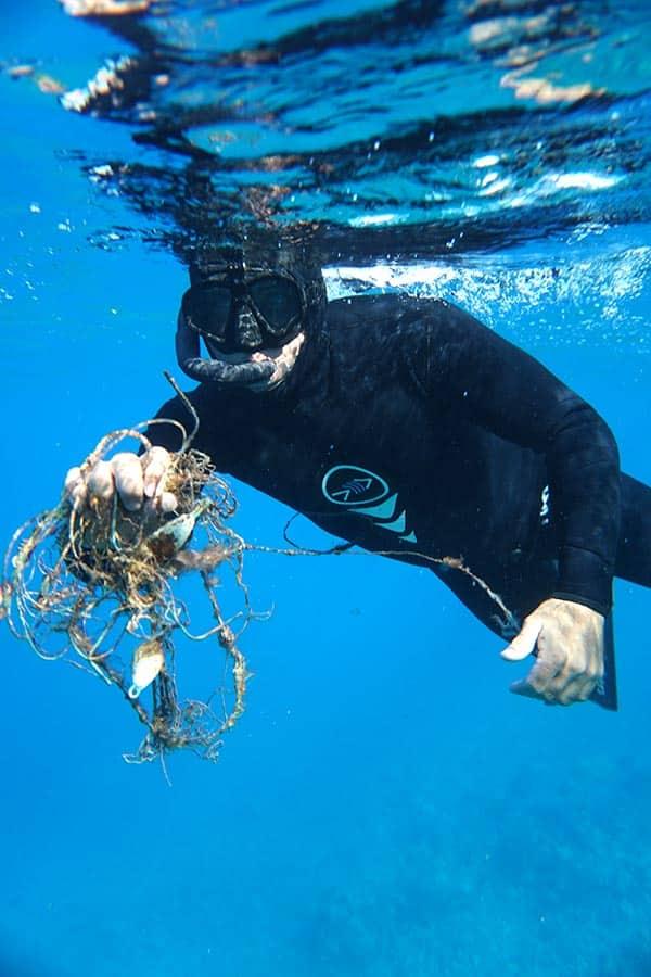 scuba diver holding trash underwater